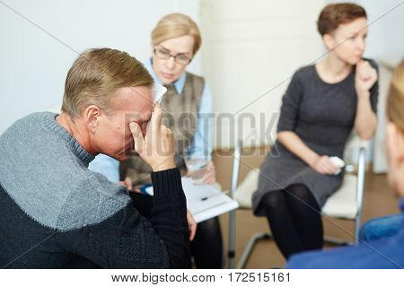 Tired man with headache visiting psychotherapist