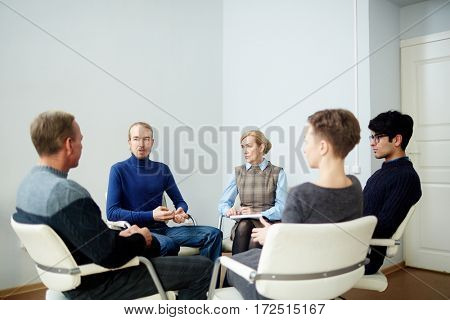 Several men and women sharing their troubles and discussing them at psychological session