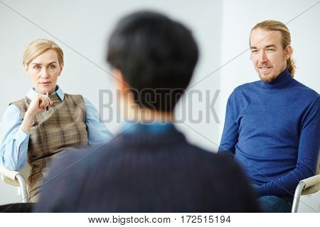 Young man and mature woman listening to story of patient