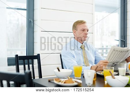 Businessman in shirt and tie reading newspaper in the kitchen at home