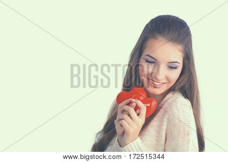 Beautiful woman hold red hear, isolated on gray background