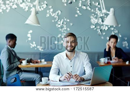 Young successful economist working with papers while sitting in cafe
