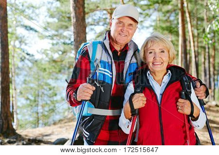Active seniors hiking with trekking sticks