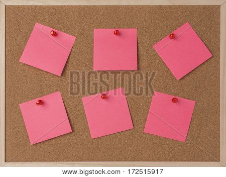 lot a pink stickry note on wooden frame cork board.
