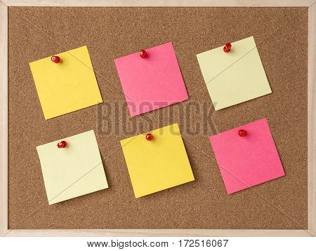 lot a yellow, pink stickry note on wooden frame cork board.