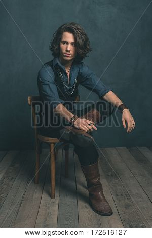 Vintage Alternative Artistic Fashion Man. Sitting On Wooden Chair In Studio.