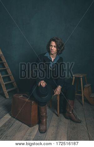 Alternative Artistic Vintage Man Wearing Black Coat. Sitting On Wooden Chair In Studio.