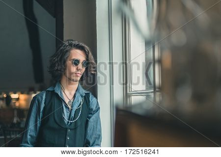 Artistic Alternative Vintage Man With Sunglasses Looking Out Window.