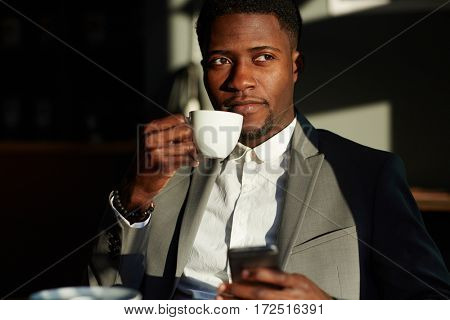 Young banker having coffee on sunny day