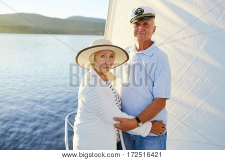 Senior couple looking at camera while traveling by yacht