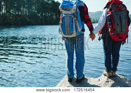 Seniors with backpacks holding by hands while standing on big stone