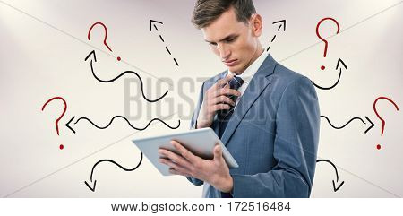 Thoughtful businessman looking at tablet pc against grey background