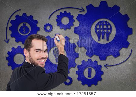 Happy businessman writing with marker against grey wall