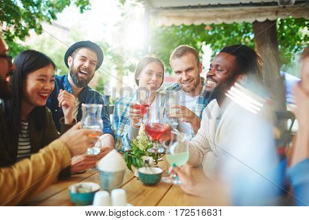 Hipster buddies with drinks having talk in outdoor cafe
