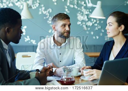 Two businessman and businesswoman discussing sales in cafe