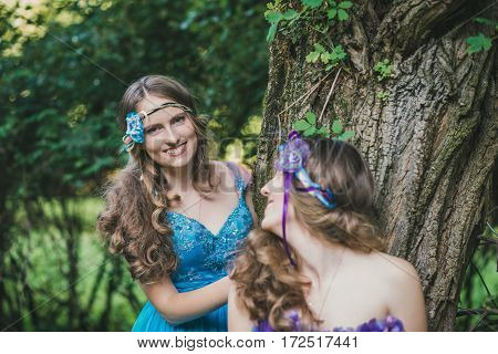 two sisters, twins from near tree in summer