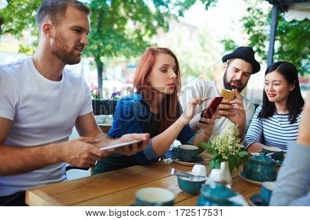 Group of modern teenagers with gadgets sitting in cafe