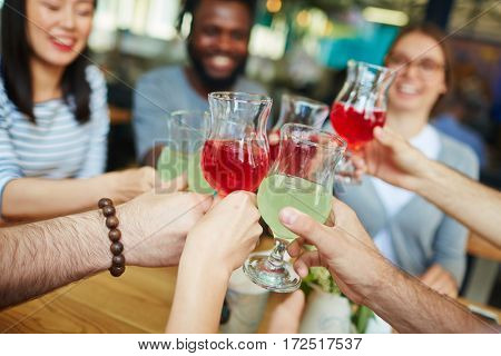 Hands of friends with glasses of drinks during toast