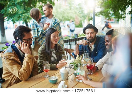 Contemporary youth with drinks spending time in outdoor cafe