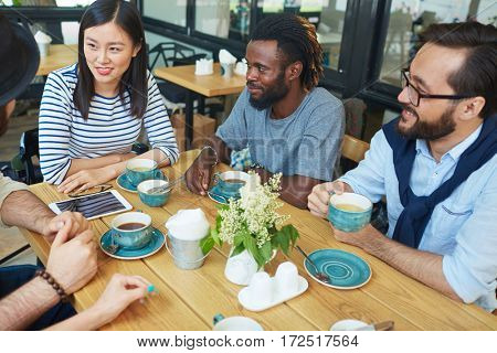 Multi-ethnic group of adolescent friends talking ni outdoor cafe