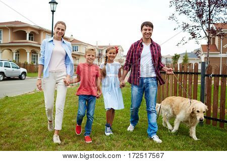 Portrait of happy family with two children, boy and girl, walking their retriever dog together on green lawn in quiet residential area
