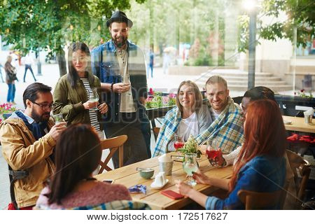 Young people communicating by drink in cafe