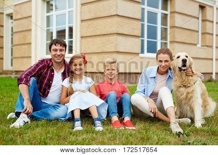 Portrait of successful happy family with two children, boy and girl, and their golden retriever dog in front of their new house, smiling and looking at camera