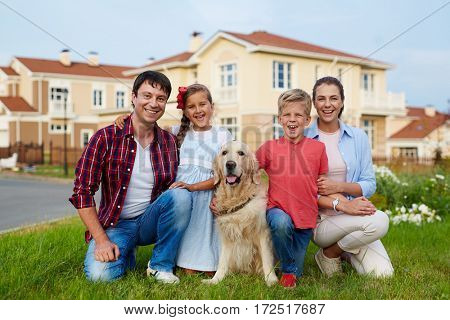 Portrait of successful happy familysitting together on green grass lawn against background of new expensive houses, smiling and looking at camera