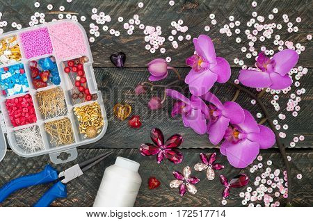 Box with beads spool of thread plier and glass hearts to create hand made jewelry on old wooden background. Handmade accessories. Orchid flowers. Top view