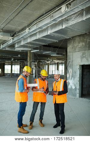 Group of three workmen discussing development progress with foreman inspector on construction site