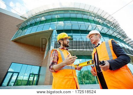Low angle view of two business people wearing protective vests and hard hats standing on construction site, executive supervisor talking to young architect in front of modern mirror glass building
