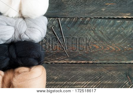 Wool for felting on old wooden background. Top view
