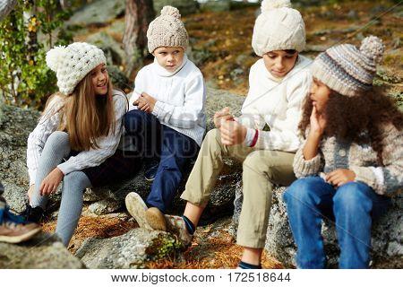 Elementary learners in casualwear talking outdoors