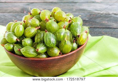 Fresh green gooseberries in a ceramic bowl on textile napkin. Gooseberry close up. Sun rays
