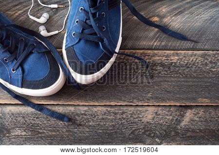 Sport shoes and earphones on old wooden background . Top view. Selective focus