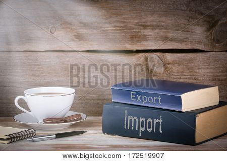 Import and Export. Stack of books on wooden desk.