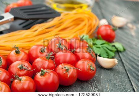 Cherry tomatoes pasta olive oil garlic herbs and pasta tongs on the old wooden background. Rustic style. Italian food. Selective focus