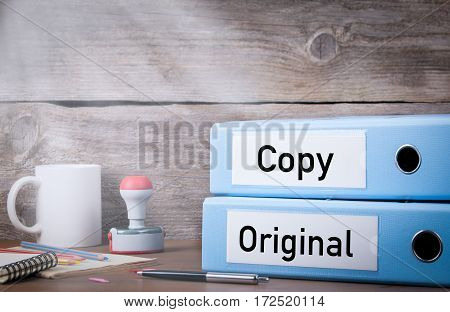 Original and Copy. Two binders on desk in the office. Business background.