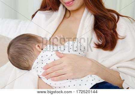 Six months old asian baby drinking breastmilk