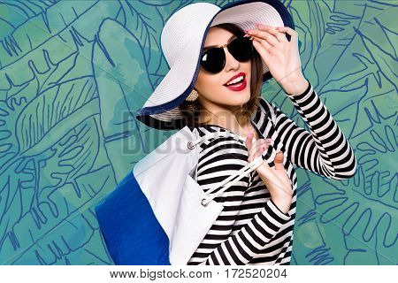 Cute smiling girl, with dark hair, wearing in striped blouse, black sunglasses and white hat, is posing with white and blue bag, on blue background with feathers, in studio, waist up