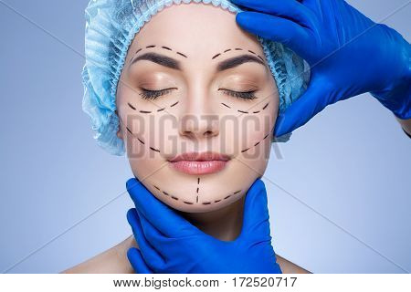Perfect girl with dark eyebrows and nude make up at blue background, doctor's hands in blue gloves touching patient's face, plastic surgery, perforation lines on face.