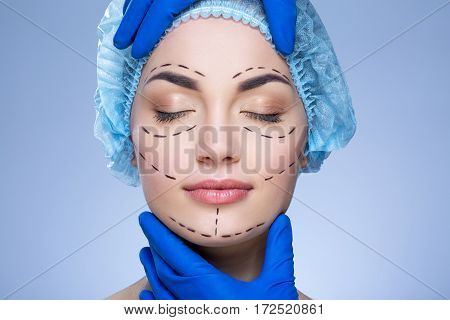 Attractive girl with dark eyebrows, closed eyes and nude make up at blue background, doctor's hands in blue gloves touching patient's face, perforation lines on face.