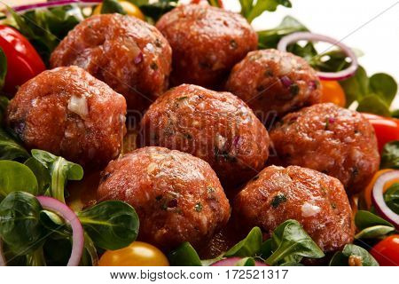 Raw meatballs on cutting board on white background
