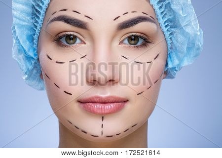 Attractive girl with dark eyebrows and naked shoulders wearing blue medical hat at blue background and looking at camera, plastic surgery, portrait, perforation lines on face.