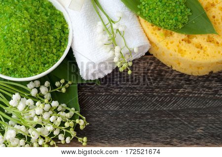 Natural green sea salt towel wisp of bast and hygiene items for bath and spa on old wooden board. Selective focus. Top view