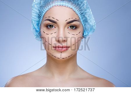Portrait of girl with dark eyebrows and naked shoulders wearing blue medical hat at blue background and looking at camera, plastic surgery, portrait, perforation lines on face.