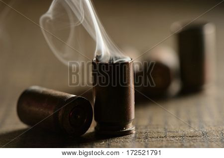 Empty 9mm bullet shell casings, on a wooden background, smoke