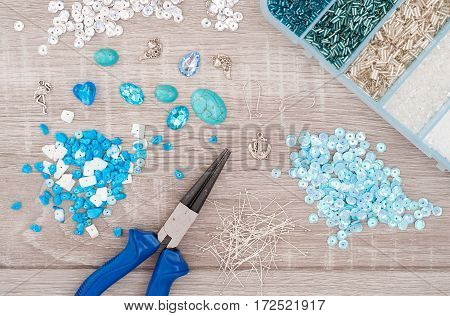 Crystals pendants charms plier glass hearts box with beads and accessories to create hand made jewelry on old wooden background. Top view