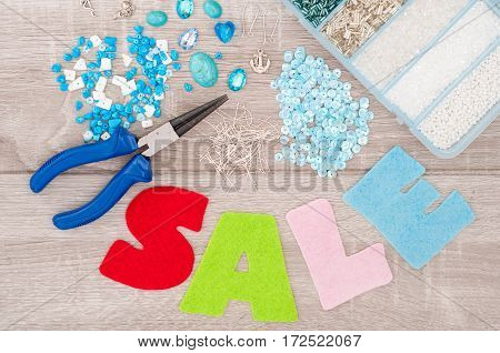 Crystals pendants charms plier glass hearts box with beads accessories to create hand made jewelry and inscription sale of felt on old wooden background. Top view. Selective focus