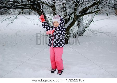 A little girl sitting on snow in winter park. She is dressed in a black jacket with white dots and pink pants and mittens.